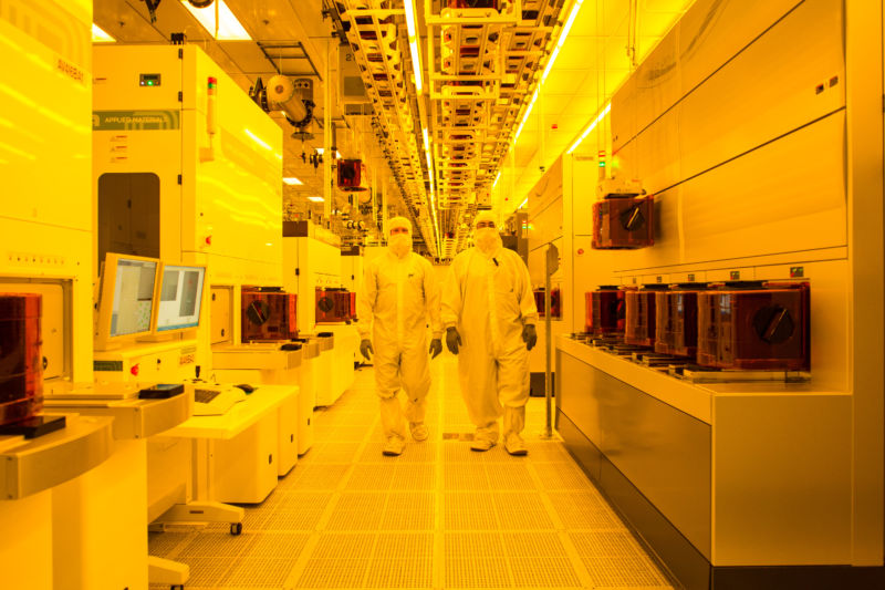 A significant portion of the Micron fab is bathed in yellow light to protect the light-sensitive coating on the wafers. Chips on the wafers are created using a photographic process. Each of the cameras, which are the machines on each side of the aisle, costs about $70 million.