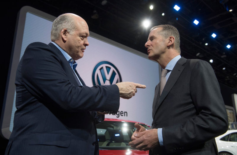 Ford CEO Jim Hackett, left, talks to Volkswagen CEO Herbert Diess in January 2019.