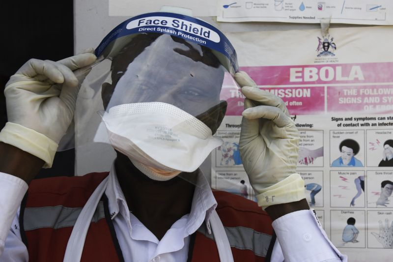 A health worker puts on protective gear as he prepares to screen travelers at the Mpondwe Health Screening Facility in the Ugandan border town of Mpondwe as they cross over from the Democratic Republic of Congo.