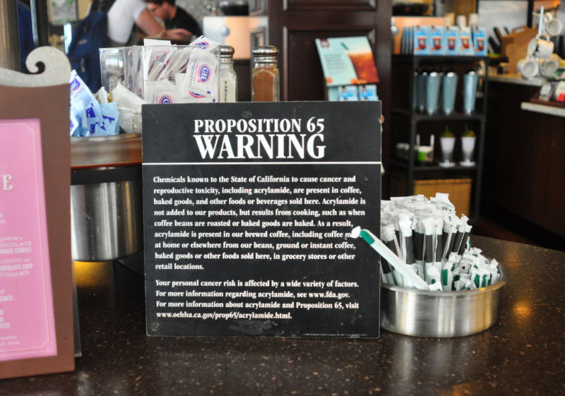 A black-and-white warning sign sits next to straws on a counter.