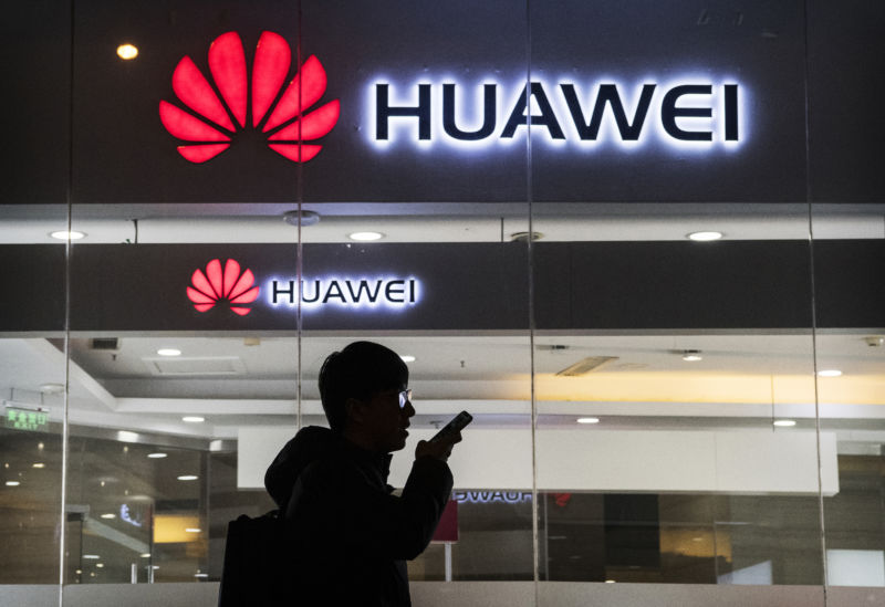 A man speaks on a smartphone outside a Huawei storefront.