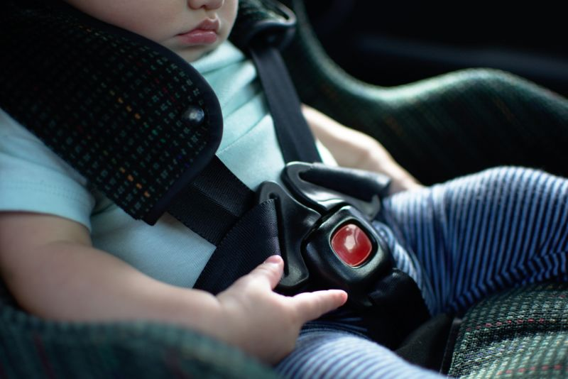 Photograph of a baby locked into a car seat.