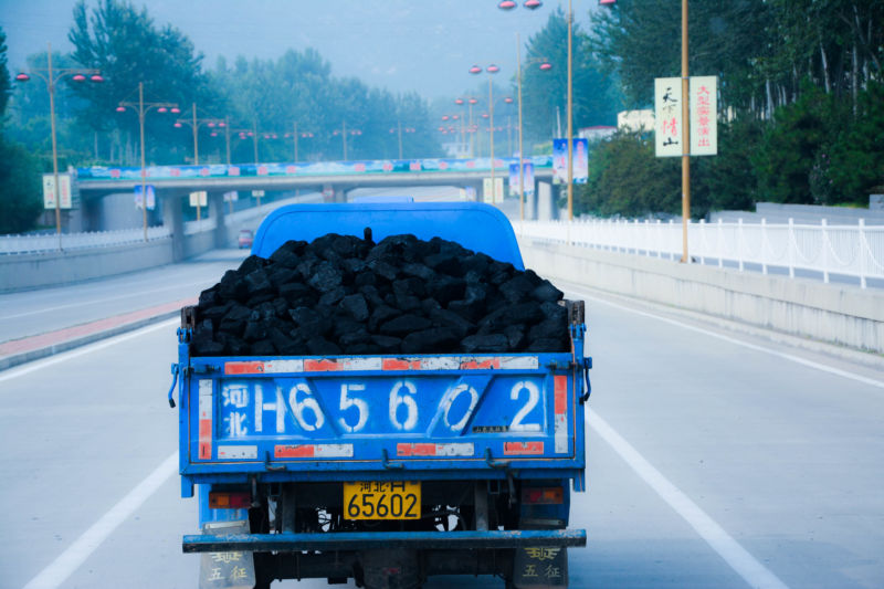 A truck filled with coal drives down a highway in China.