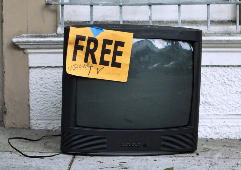 A TV set left on a sidewalk with a sign that says,