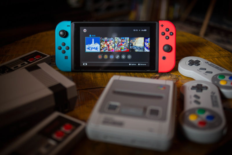a Nintendo Switch (M) surrounded by a NES (Nintendo Entertainment System) Classic Mini (L) and a SNES (Super Nintendo Entertainment System) Classic Mini (R) video game consoles.