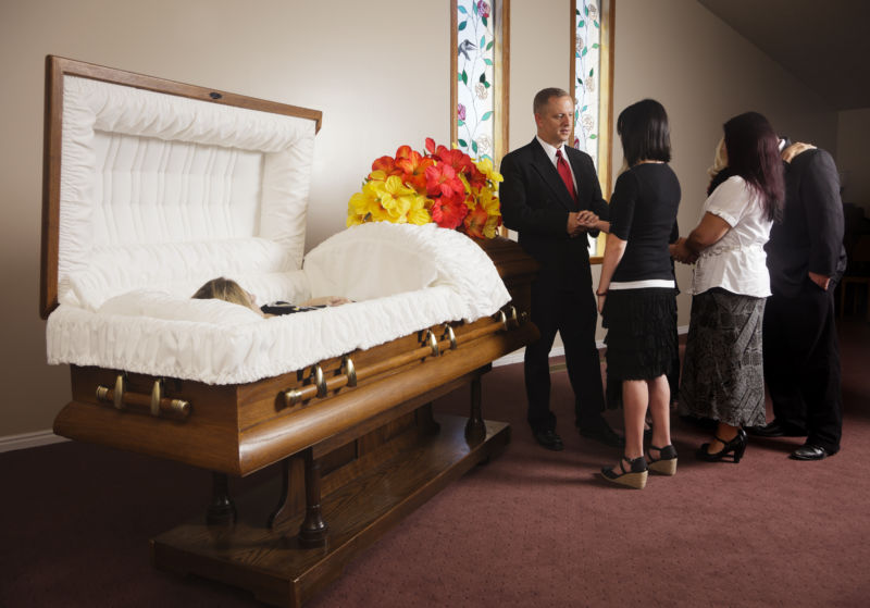 A receiving line of guests next to the casket at a funeral in a funeral home.