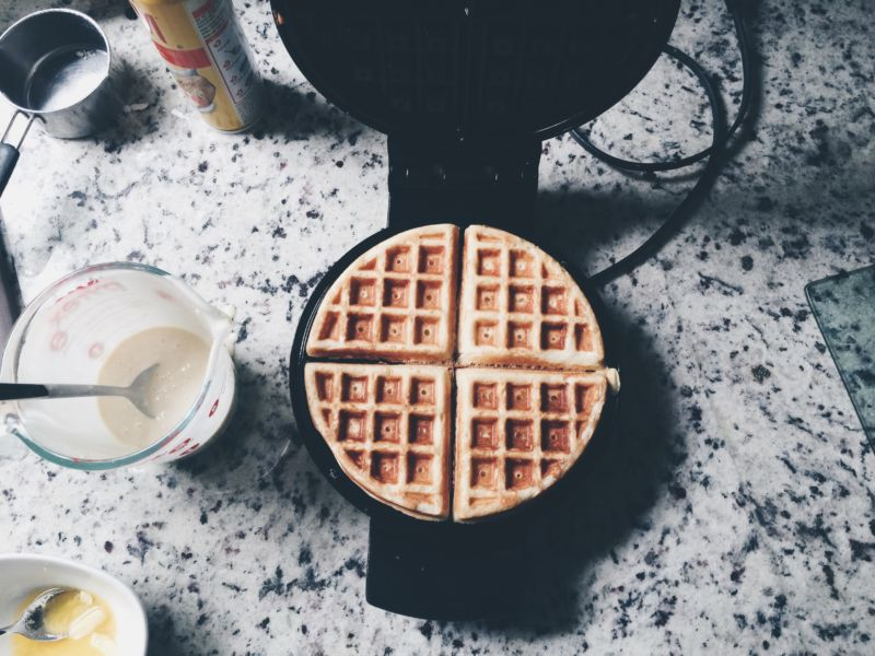 "Where can we volunteer to be a stock photographer of waffle imagery? ""High Angle View Of Waffles On Iron."""