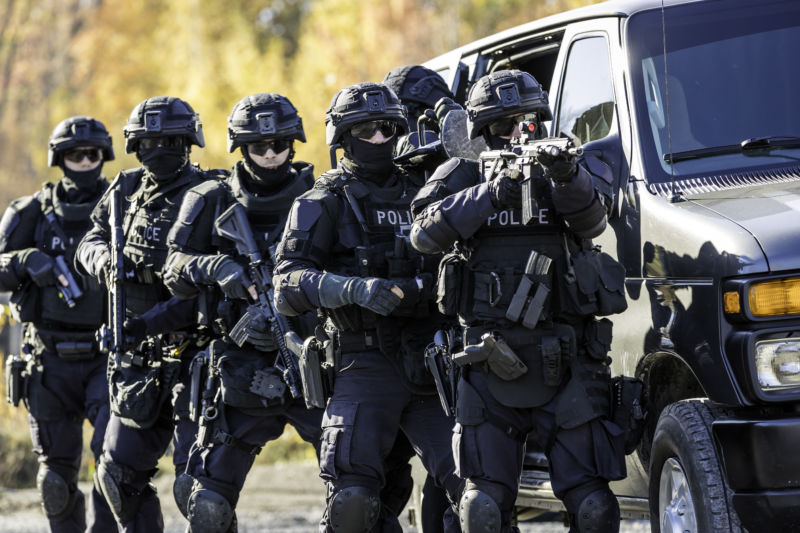 Heavily armed men in body armor stand ready behind a van.