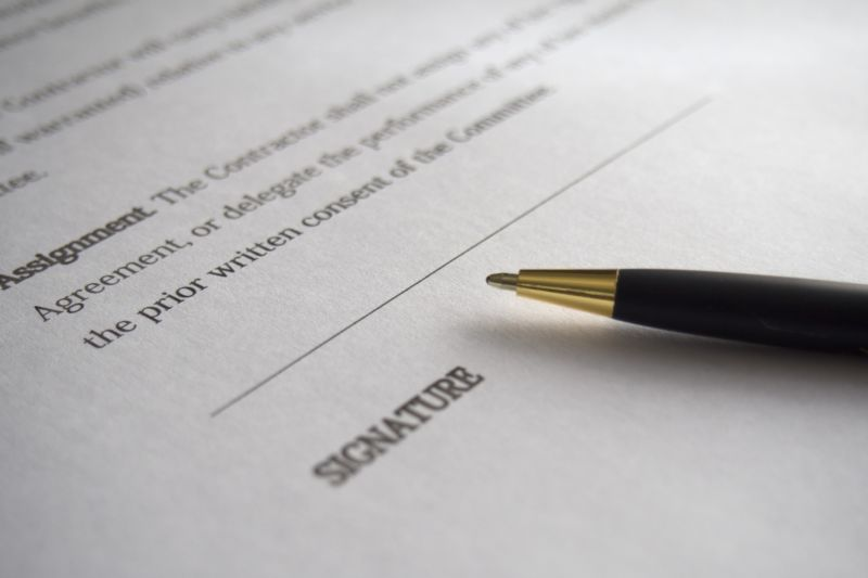 Extreme closeup of a pen next to a signature line on a legal document