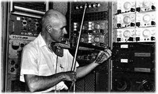 "Max Mathews plays one of the electronic violins he built in his analog electronics lab at Bell Labs. (Credit: <a href=""http://www.seamusonline.org/max.html"">Wikimedia / Society for Electro-Acoustic Music in the US</a>"