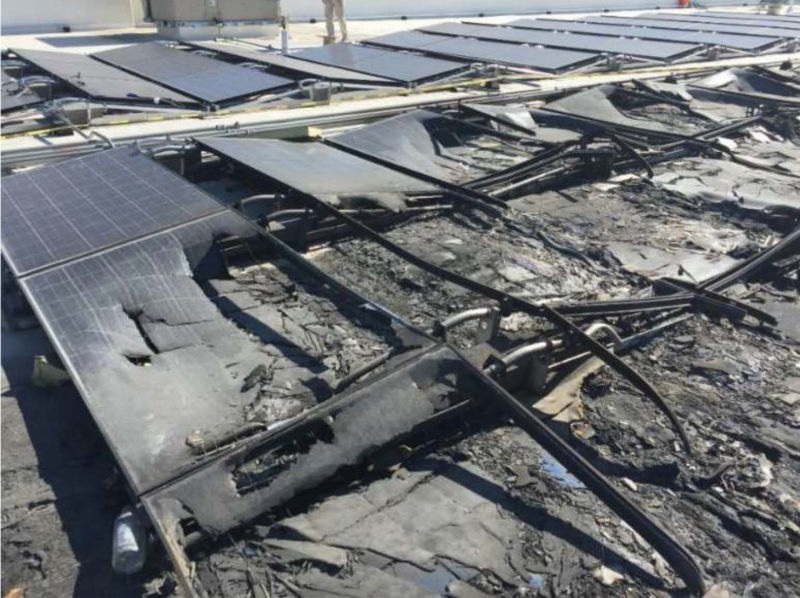 A photo from Walmart's lawsuit shows charred solar panels on top of a Walmart store.