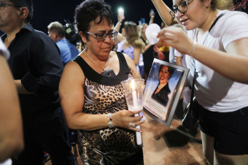 At an interfaith vigil for victims of a mass shooting in El Paso, Texas, a woman carries a candle and a photo of Elsa Mendoza Marquez, who died in the shooting.