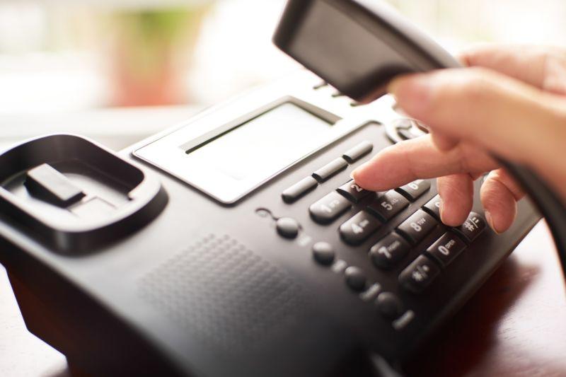 A person's hand dials a landline phone.