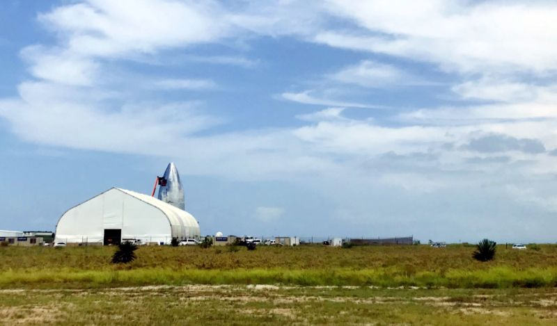 The nose cone of Starship Mk1 peeks out from behind SpaceX facilities in Boca Chica on July 24.