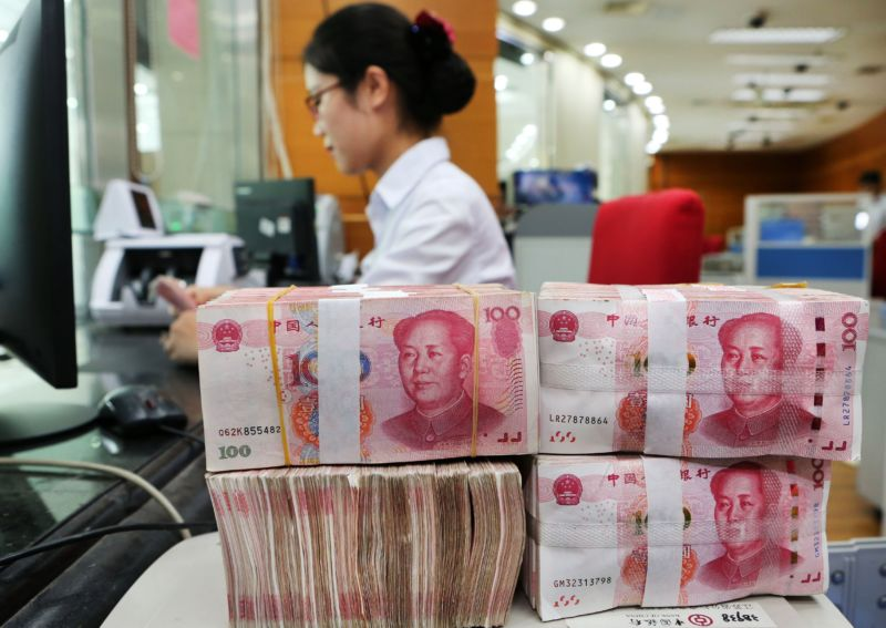 An employee counts 100-yuan notes at a bank in Nantong in China's eastern Jiangsu province on July 23, 2018.