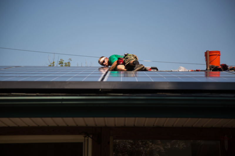 A man in construction gear assembles a solar panel on a residential roof.