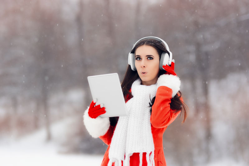 Stock photo of young woman wearing headphones in snow.