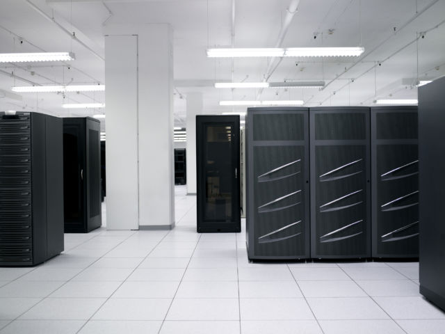 A data center stock photo. I spy with my little eye some de-badged EMC Symmetrix DMX-3 or DMX-4 disk bays at right and some de-badged EMC CX disk bays at left. Disk arrays like these are a mainstay of traditional enterprise datacenter SANs.