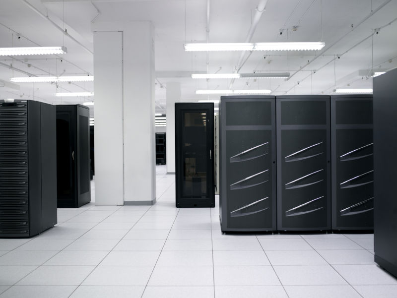 A data center stock photo. I spy with my little eye some de-badged EMC Symmetrix DMX-3 or DMX-4 disk bays at right and some de-badged EMC CX disk bays at left. Disk arrays like these are a mainstay of traditional enterprise data center SANs.