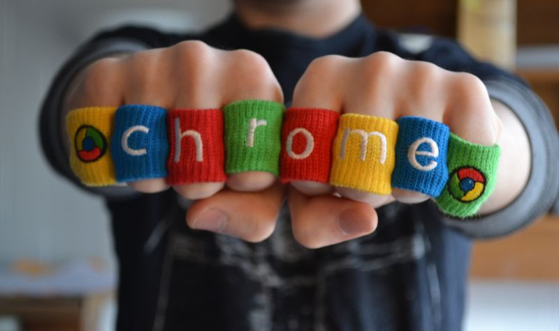 A man wears soft rings that spell out CHROME.