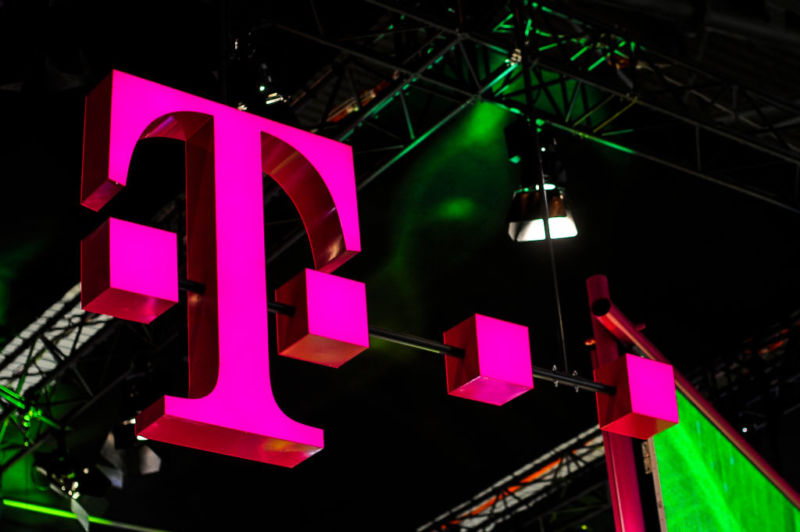 The logo of Deutsche Telekom, owner of T-Mobile, seen over a booth at the Mobile World Congress expo hall.