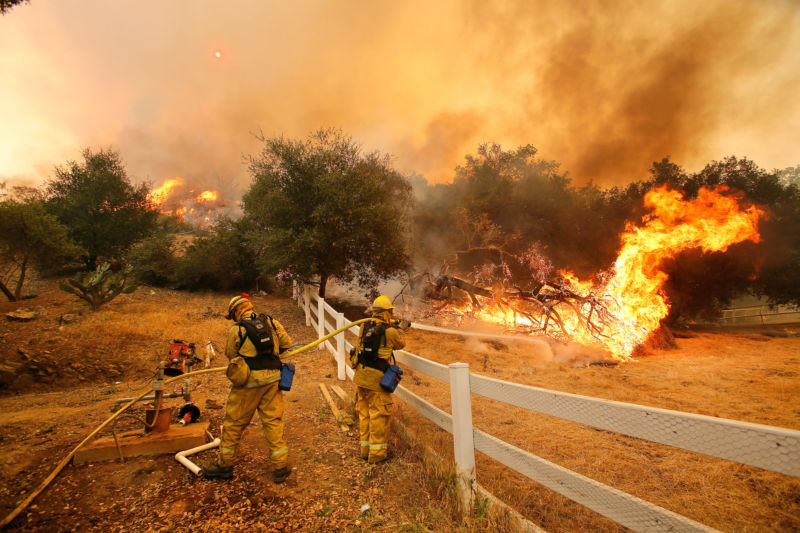 Firefighters from Stockton, Calif.,  put out flames off of Hidden Valley Rd. while fighting a wildfire, Friday, May 3, 2013 in Hidden Valley, Calif.  (AP Photo/Los Angeles Times, Mel Melcon)