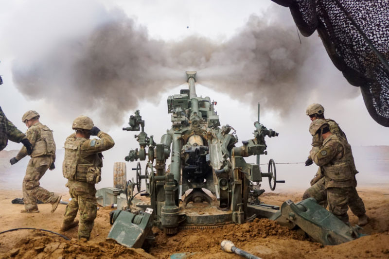 Soldiers in combat gear fire a gigantic gun.