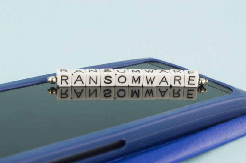 Scrabble letters sitting atop laptop computer spell Ransomware.