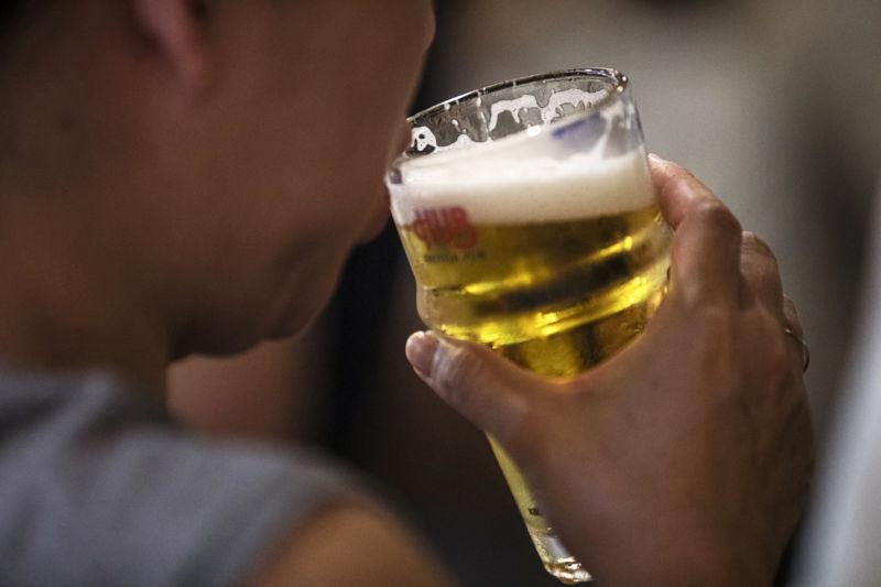Man sips a beer.