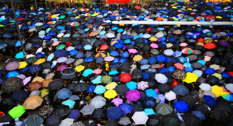 Hong Kong protestors beneath umbrellas.
