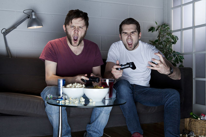 Stock photo of angry young men playing video games.