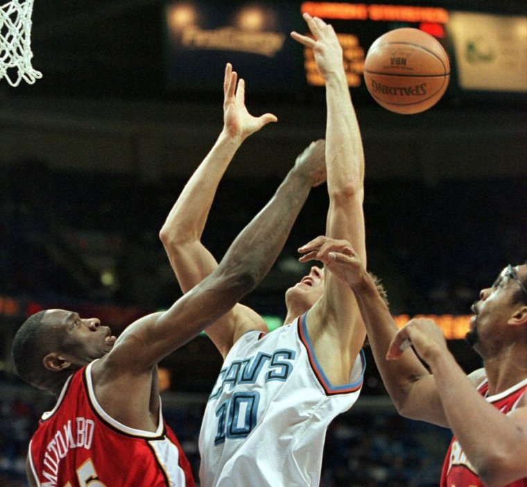 Image of a basketball player having his shot blocked.