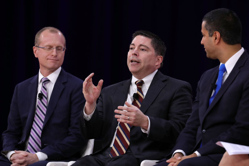 FCC Commissioner Michael O'Rielly speaks at a conference while FCC Commissioner Brendan Carr and Chairman Ajit Pai look on.