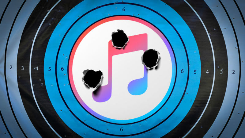 The iTunes logo has been photoshopped onto a pistol target that has been shot multiple times.