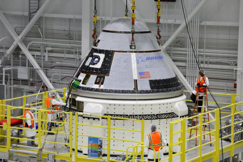 Orange workers are present in a space capsule in a giant hangar.
