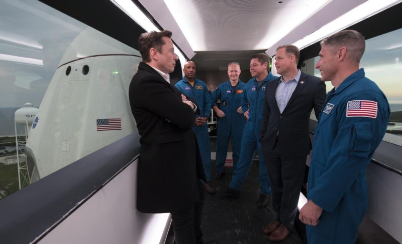 SpaceX CEO and Chief Designer Elon Musk, left, NASA astronauts Victor Glover, Doug Hurley, Bob Behnken, NASA Administrator Jim Bridenstine, and NASA astronaut Mike Hopkins are seen inside the Dragon crew access arm at Launch Complex 39A in March.
