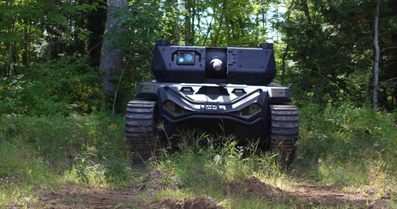 A uncrewed tank rolls through a forest.