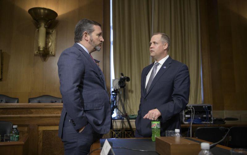 Doi bărbați în costume vorbesc între ei.
