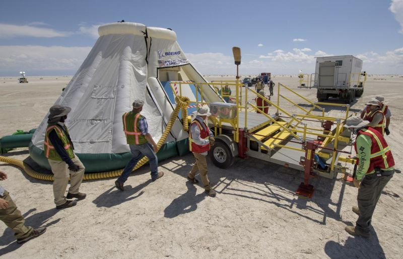 People in security equipment work on a spacecraft in the desert.