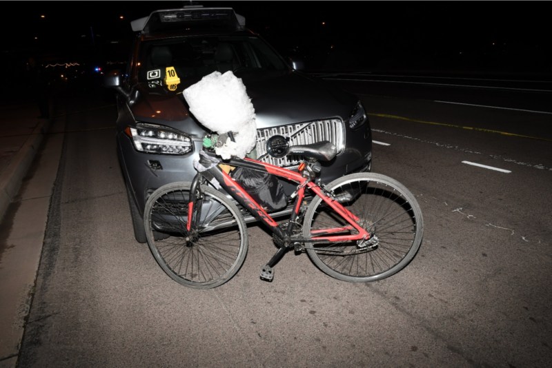 A bicycle leans against the front of an SUV at night.