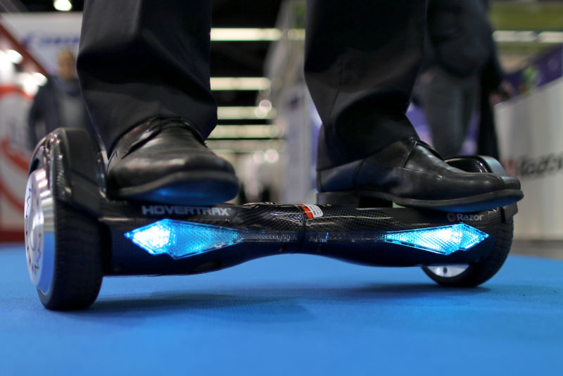 Close-up photograph of feet on hoverboard on institutional floor.