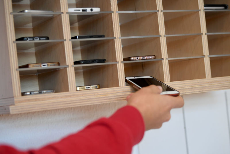 Picture of someone putting their smartphone into a storage cubby before class.