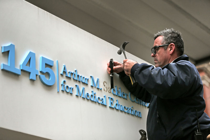Tufts employee Gabe Ryan removes letters from signage featuring the Sackler family name at the Tufts building at 145 Harrison Ave. in Boston on Dec. 5, 2019.