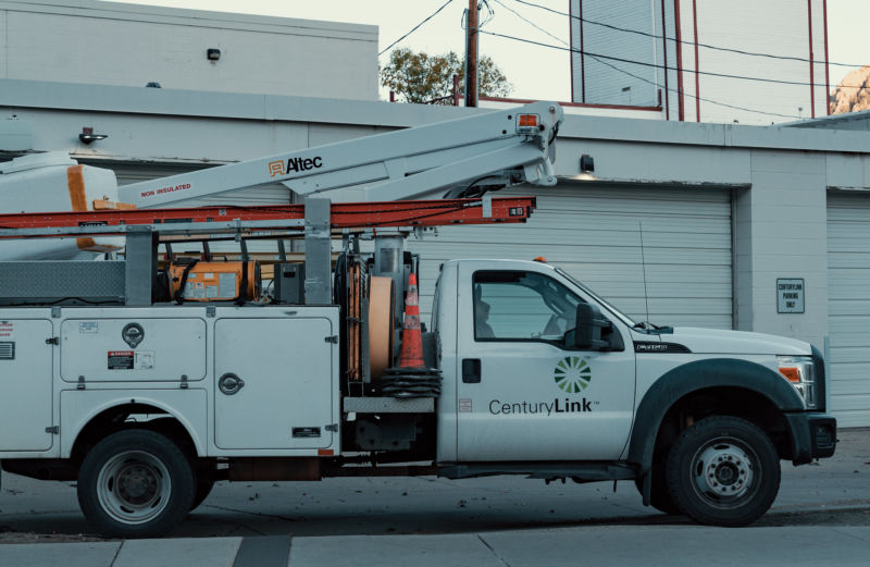 A white truck with a CenturyLink logo is parked next to a building.