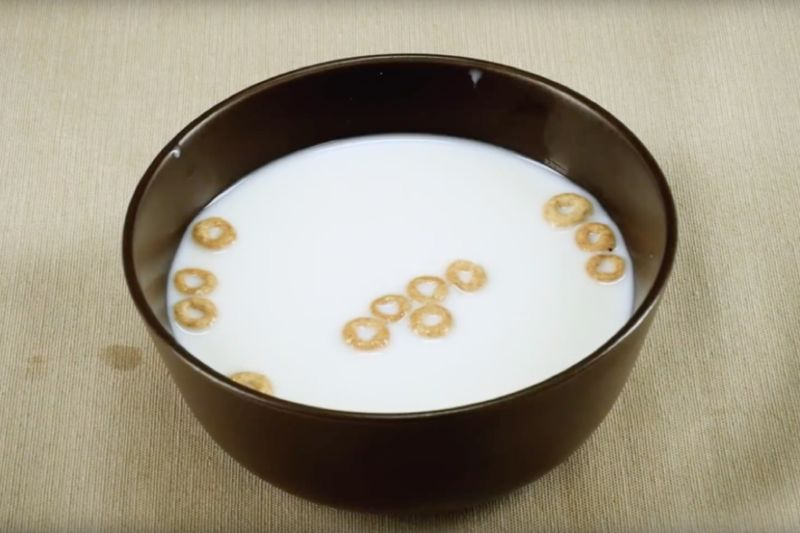 Image of a bowl of milk with a handful of Cheerios floating in it.