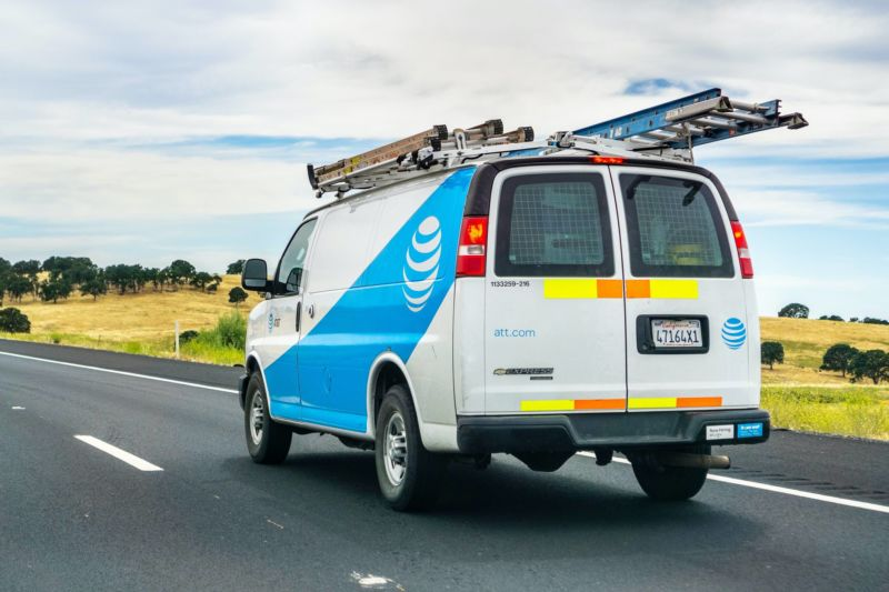 An AT&T service van driving on a freeway.