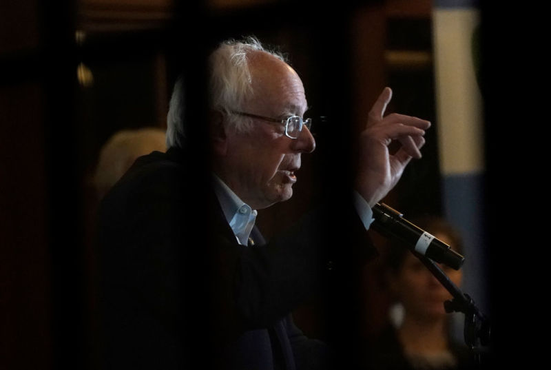 Bernie Sanders speaking into a microphone and gesturing with his hand.