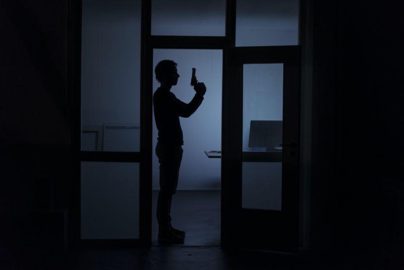 A man holding a gun, seen in a dark office.