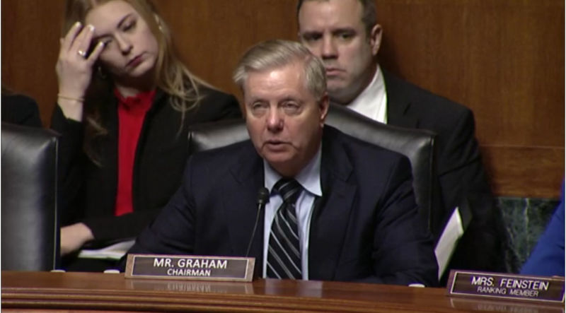 A serious man in a suit speaks during a senate hearing.