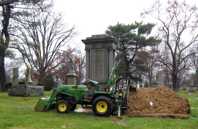 Stock photo of a gravedigging machine in front of a headstone.